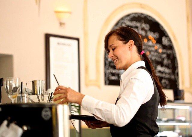 kelnerka niosąca zamówienie schludnie ubrana, systemy przywoławcze w restauracji