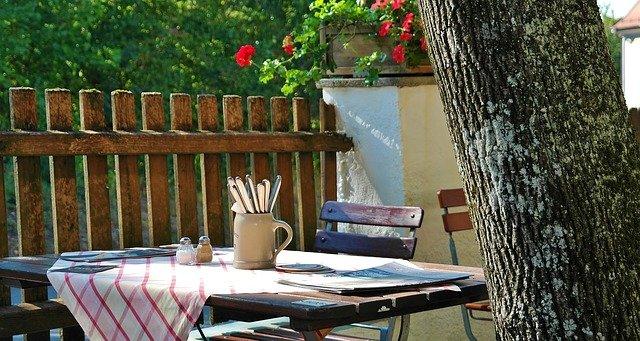 ogródek restauracji, widać stolik i krzesła, obrus w różową kratę, tu znajduje zastosowanie system przywoływania klienta w gastronomii